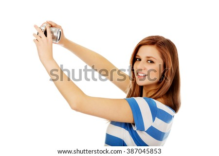 Happy teenage woman taking selfie with classic slr camera - stock photo