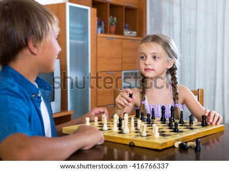 Happy teenager and little girl playing chess in home interior. Focus on the girl - stock photo