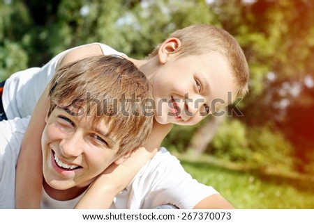Happy Teenager and Little Kid Portrait outdoor - stock photo