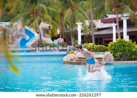 Happy teenager boy jumping in a swimming pool playing with his father enjoying summer vacation in a beautiful tropical resort - stock photo