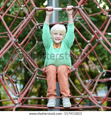 Happy teenager boy plays outdoors at playground hanging in the net - stock photo