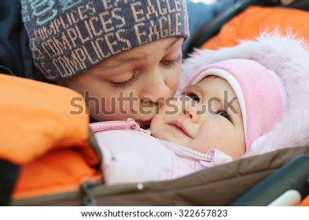 Happy teenager brother kissing baby sister in a stroller, outdoor portrait - stock photo