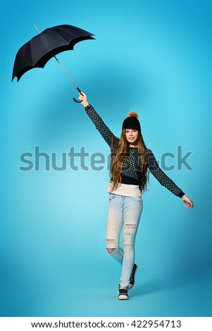 Happy teenager girl in spring clothes holding umbrella and smiles. Modern teen generation. Youth fashion. Demi-season clothes. Full length portrait. - stock photo