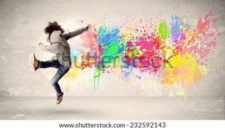 Happy teenager jumping with colorful ink splatter on urban background concept - stock photo