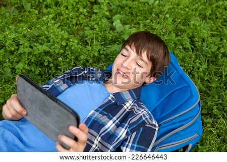 Happy teenager lying on grass in park with tablet, outdoor, schoolboy - stock photo