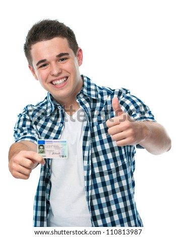 happy teenager showing his driving license - stock photo