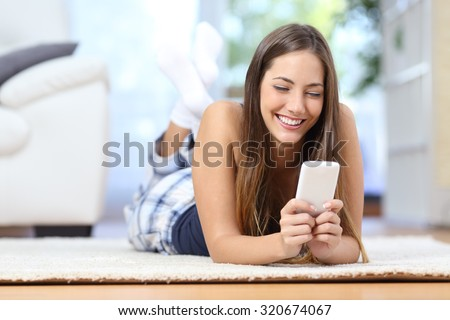 Happy teenager texting on the mobile phone lying on a carpet in the living room - stock photo