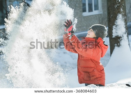 Happy teenager tossing up natural snow in frosty winter sunny day outdoors - stock photo