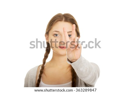 Happy teenager with victory gesture. - stock photo