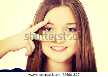 Happy teenager with victory sign on eye. - stock photo