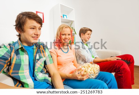 Happy teenagers hold popcorn and sit on sofa - stock photo
