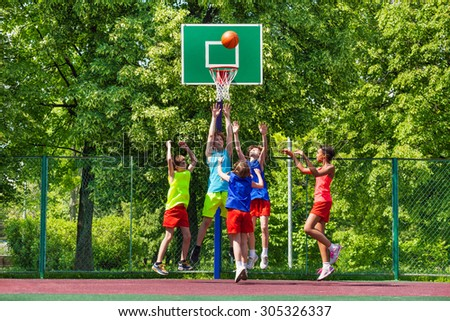 Happy teenagers playing basketball on playground - stock photo