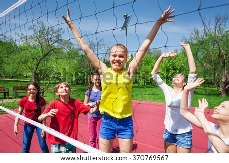 Happy teenagers playing near the volleyball net - stock photo
