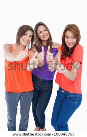 Happy teenagers putting their thumbs up - stock photo