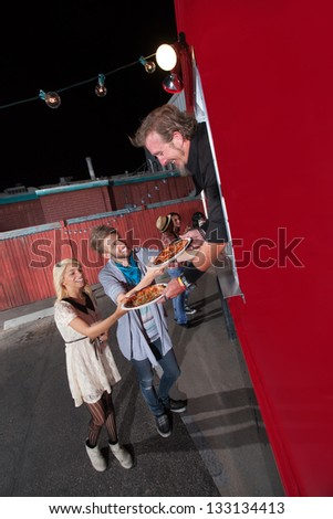 Happy teenagers served pizza from food truck owner - stock photo