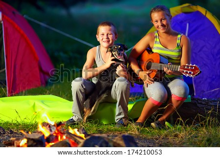 happy teenagers singing songs around camp fire - stock photo
