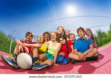 Happy teenagers who sit on volleyball game court - stock photo