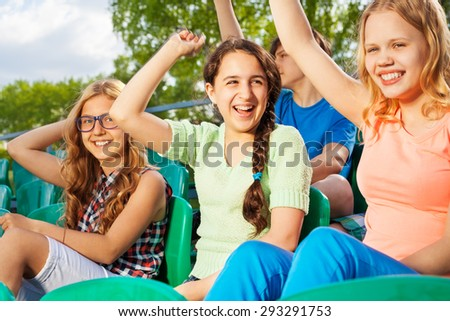 Happy teens cheering for team sitting on tribune - stock photo