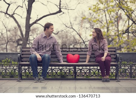 Happy teens sitting at the bench at alley at the park - stock photo