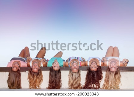 happy teens with long healthy hair laying upside down.  - stock photo