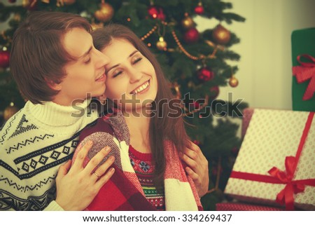 happy tender loving couple in an embrace warmed at Christmas tree  - stock photo