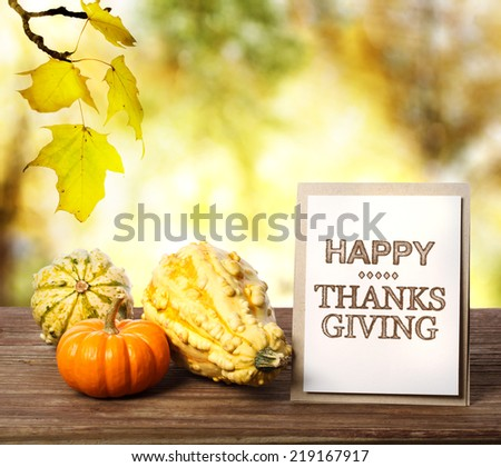 Happy Thanksgiving message card with pumpkins over yellow leaves - stock photo