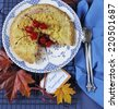 Happy Thanksgiving table setting with cherry apple crumble pie on a vintage blue plate with autumn leaves on blue tablecloth. Close up. - stock photo