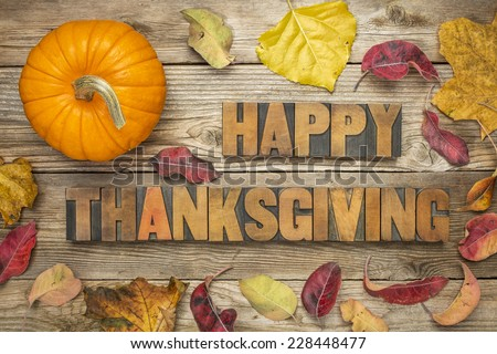 Happy Thanksgiving  - text in vintage letterpress wood type blocks against rustic wood background with a pumpkin and dry leaves - stock photo