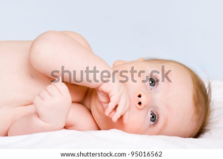 happy the child is lying on its side and looks toward - stock photo