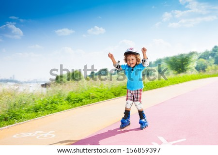 Happy thee years old boy rollerblading with lifted hands in the park on sunny summer day with bike and pedestrian signs on the road - stock photo