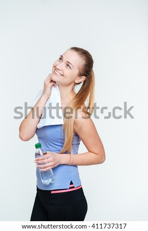 Happy thoughtful fitness woman looking up at copyspace isolated on a white background - stock photo