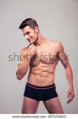 Happy thoughtful muscular man standing over gray background - stock photo