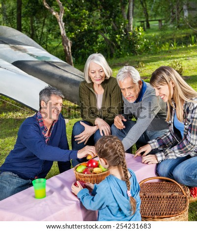 Happy three generation family having fruits in park at campsite - stock photo