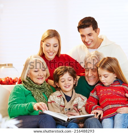 Happy three generation family reading story book at christmas - stock photo