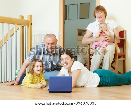 Happy three generations family at floor in home - stock photo