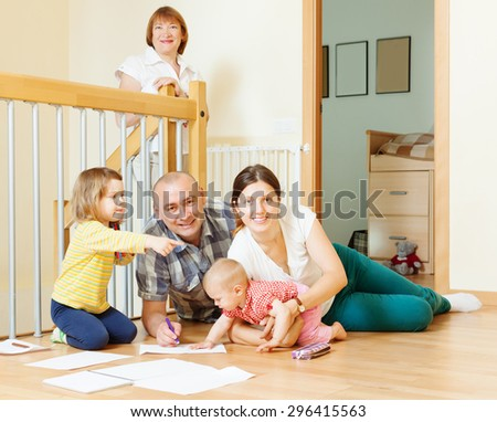 happy three generations family with two children enjoying at floor in home   - stock photo