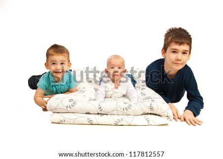 Happy three kids ,brothers lying down  in a line isolated on white background - stock photo