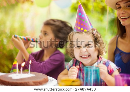 Happy three years old girl at her birthday party. Loving her cake - stock photo
