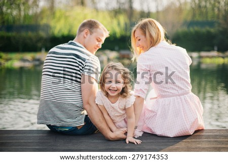 Happy to be a family. Close-up of loving family having fun while sitting on the pier - stock photo