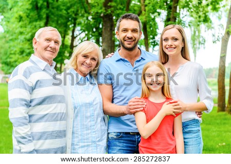 Happy to be a family. Happy family of five people bonding to each other and smiling while standing outdoors together  - stock photo