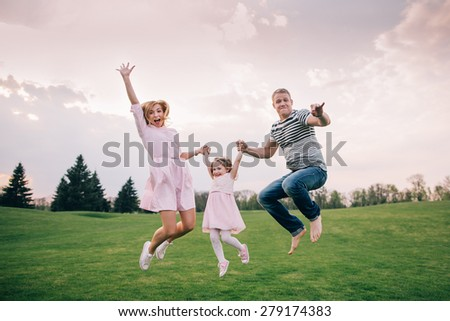 Happy to be a family. Happy family of three jumping and laughing outdoors - stock photo