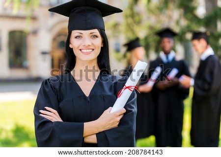 Happy to be graduated. Happy young woman in graduation gowns holding diploma and smiling while her friends standing in the background  - stock photo