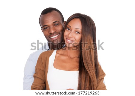 Happy to be together. Beautiful young African couple standing close to each other and smiling at camera while isolated on white  - stock photo
