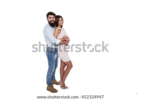 Happy to be together. Beautiful young couple standing close to each other and smiling at camera while isolated on white. - stock photo