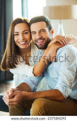 Happy to be together. Beautiful young loving couple sitting together on the couch while woman embracing her boyfriend and smiling  - stock photo