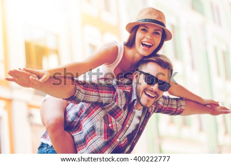 Happy to be together. Happy young man piggybacking his girlfriend while keeping arms outstretched  - stock photo