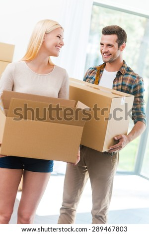 Happy to start a new life together. Happy young couple holding a cardboard box and looking at each other while other carton boxes laying on background - stock photo