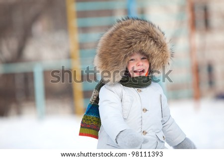 Happy toddler boy in winter jacket with fur trim - stock photo