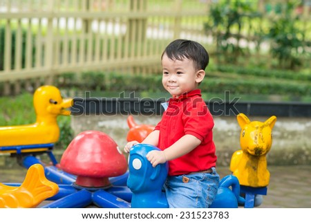 Happy toddler boy looking down to camera. Smiling little boy playing on playground. Summer park. Outdoors. - stock photo