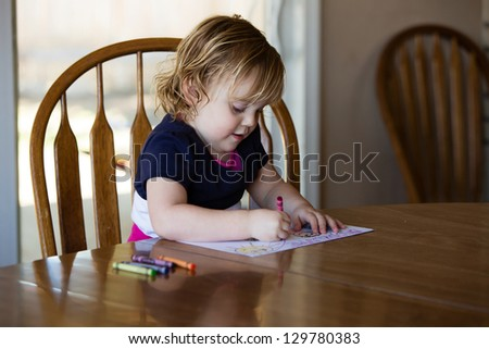 Happy toddler girl coloring - stock photo